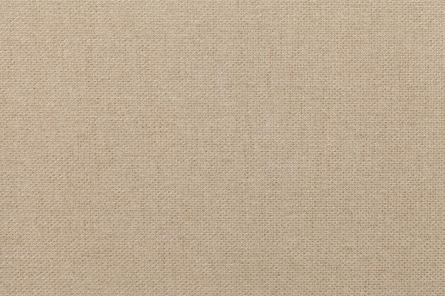 Fond beige clair en matière textile, tissu à texture naturelle,