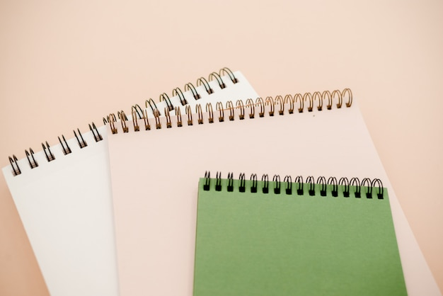 Fond beige avec espace copie avec un style minimal de cahiers blanc et vert.