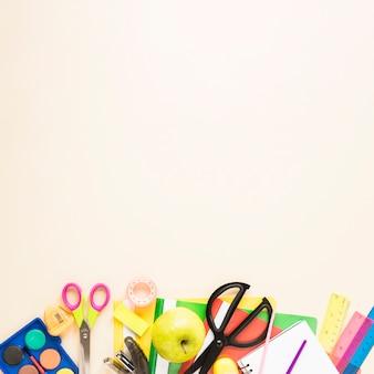 Fond beige avec des fournitures scolaires