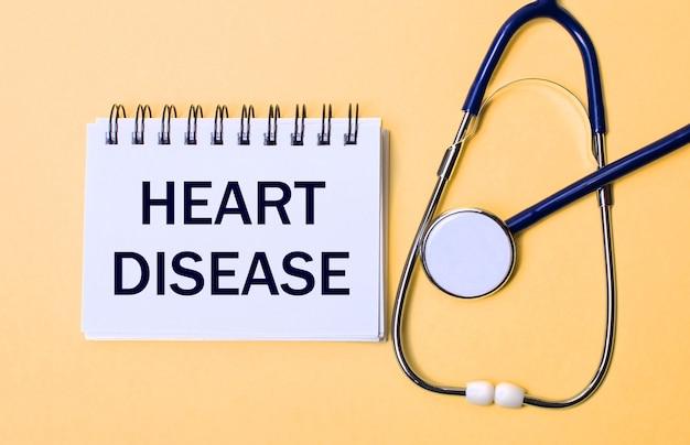Sur fond beige, un stéthoscope et un bloc-notes blanc avec l'inscription heart maladie. concept médical