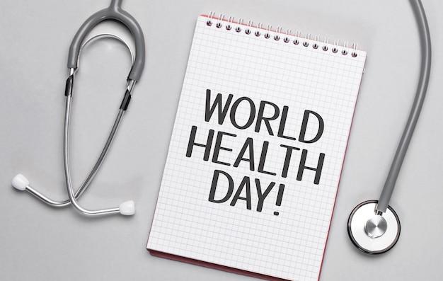Sur fond beige, un stéthoscope et un bloc-notes blanc avec l'inscription journée mondiale de la santé.