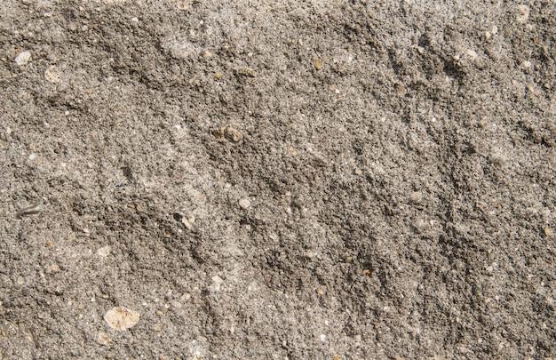 Fond de béton gris. fond de mur de pierre fissuré. béton relief gris.