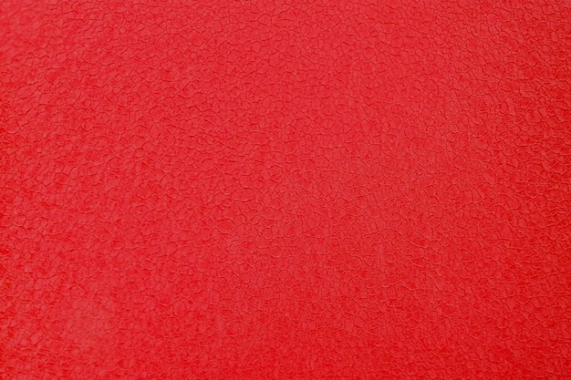 Fond de béton de mur de ciment ancien rouge texturé.