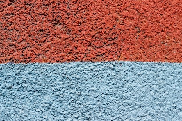 Fond en béton peint avec de la peinture orange et bleue.