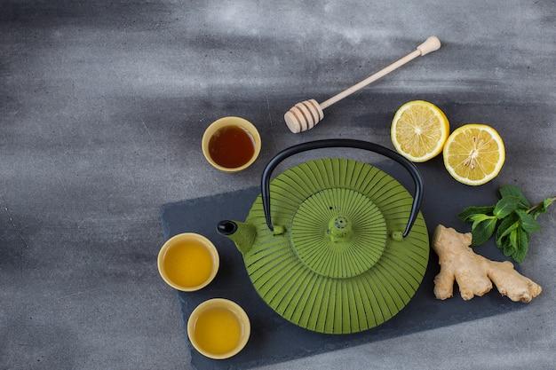 Sur un fond de béton, une théière sur un plateau, du thé dans un bol, du gingembre, du miel, de la menthe et du citron