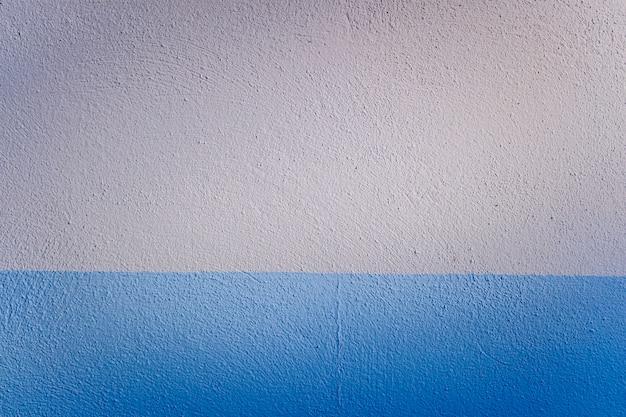Fond bicolore bleu et blanc d'un mur texturé éclairé latéralement par la lumière du soleil.