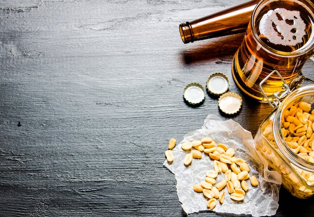Fond de bière. bière aux arachides sur la table en bois noire