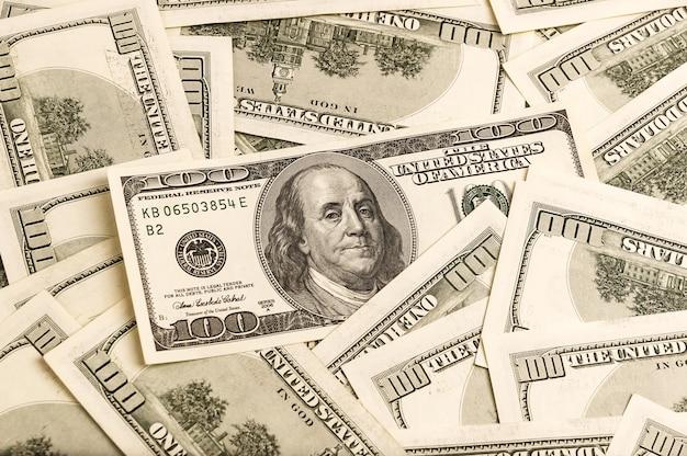 Un fond de billets de cent dollars dans un style vintage en mettant l'accent sur l'un des billets.