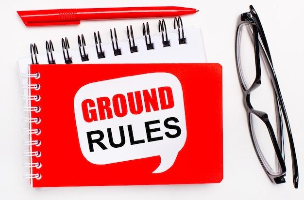 Sur un fond blanc, des blocs-notes blancs et rouges, des lunettes noires, un stylo rouge et une carte blanche avec le texte règles de base