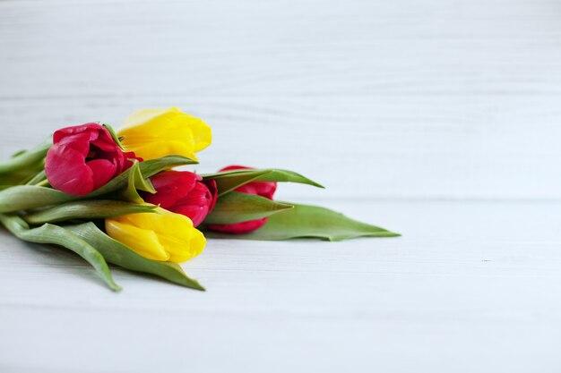 Fond blanc en bois et fleurs jaunes et rouges.