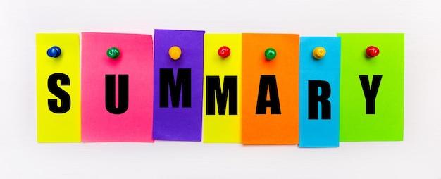 Sur un fond blanc, des boutons sont utilisés pour fixer des bandes de papier multicolores lumineuses avec le texte résumé