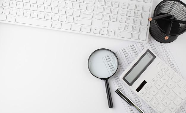 Fond blanc avec clavier, graphique, calculatrice et loupe. espace de copie