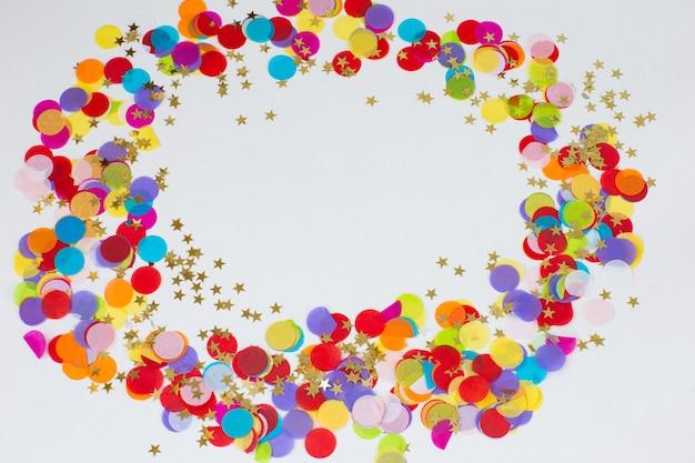 Sur un fond blanc, des confettis colorés et des étoiles dorées sont alignés dans un cercle