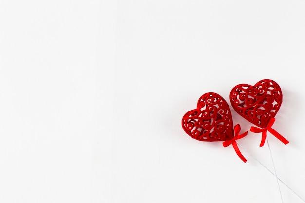 Sur fond blanc deux coeurs ajourés rouges