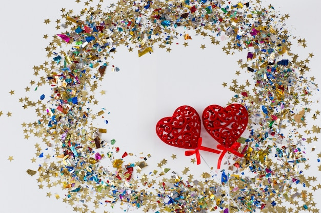 Sur un fond blanc deux coeurs rouges ajourés et beaucoup de confettis colorés autour