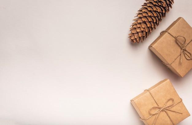 Fond blanc eco avec deux coffrets cadeaux avec des arcs de ficelle de jute et pomme de pin avec espace de copie.