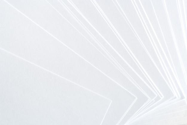 Fond blanc de feuilles de papier propres disposées négligemment.