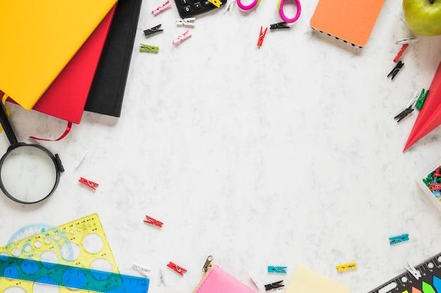 Fond blanc avec des fournitures scolaires et des manuels scolaires