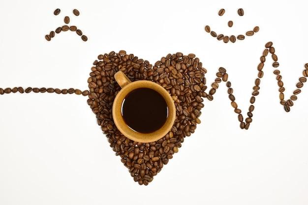Sur un fond blanc il y a une tasse de café une forme de coeur est présentée des grains de café