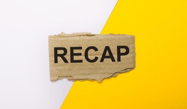 Sur fond blanc et jaune, carton marron déchiré avec le texte recap