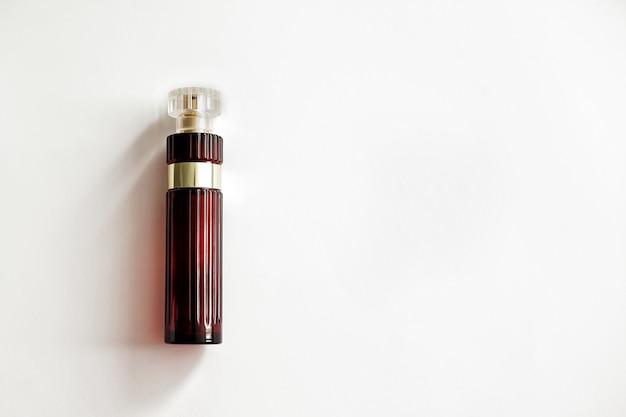 Sur un fond blanc se trouve une bouteille en verre de parfum de couleur rouge foncé.