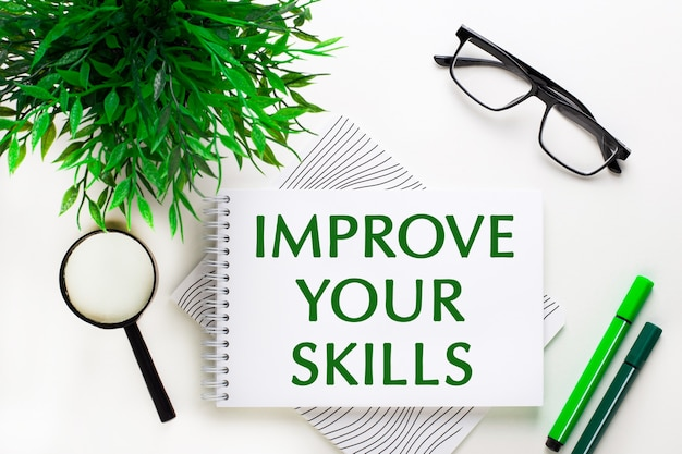 Sur un fond blanc se trouve un cahier avec des mots améliorez vos compétences, des lunettes, une loupe, des marqueurs verts et une plante verte