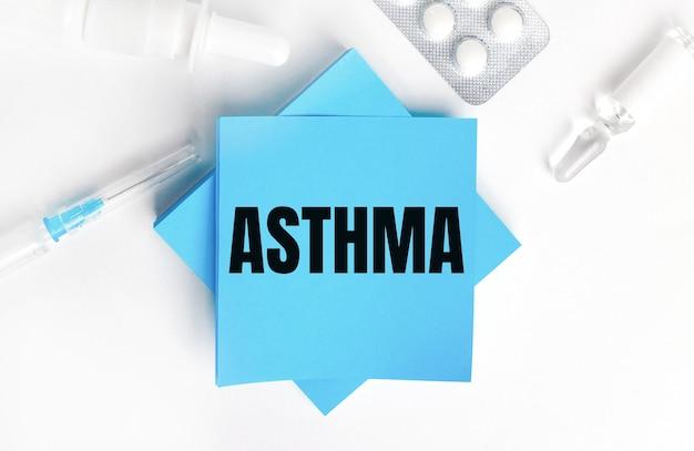 Sur fond blanc, une seringue, une ampoule, des pilules, un flacon de médicament et des autocollants bleu clair avec l'inscription asthma. concept médical