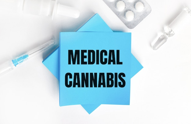 Sur fond blanc, une seringue, une ampoule, des pilules, un flacon de médicament et des autocollants bleu clair avec l'inscription cannabis médical. notion médicale