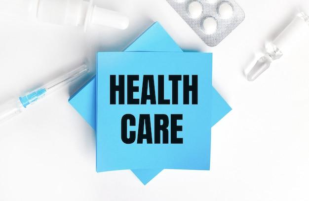 Sur fond blanc, une seringue, une ampoule, des pilules, un flacon de médicament et des autocollants bleu clair