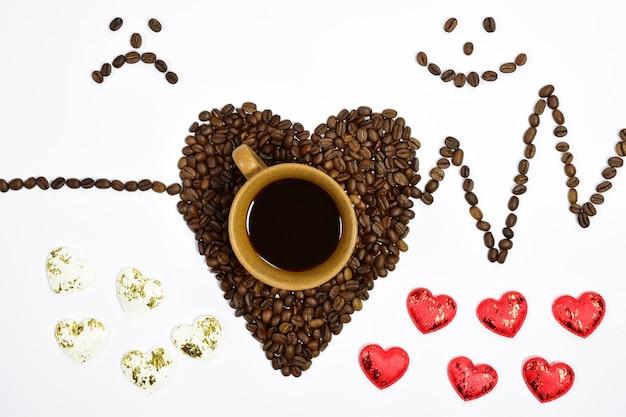 Sur un fond blanc, une tasse de café en dessous est une forme de coeur faite de grains de café