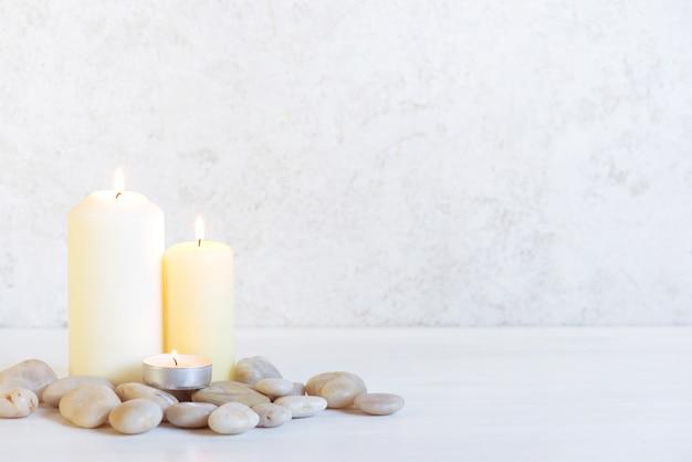 Fond blanc avec trois bougies allumées et pierres