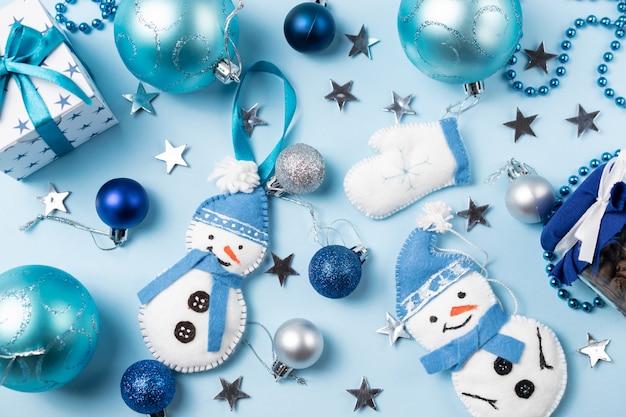 Fond bleu avec des boules de noël, bonhomme de neige en feutre, mitaines et décorations