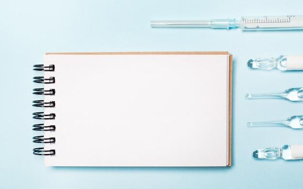 Sur un fond bleu clair, des ampoules, une seringue et un cahier vierge.