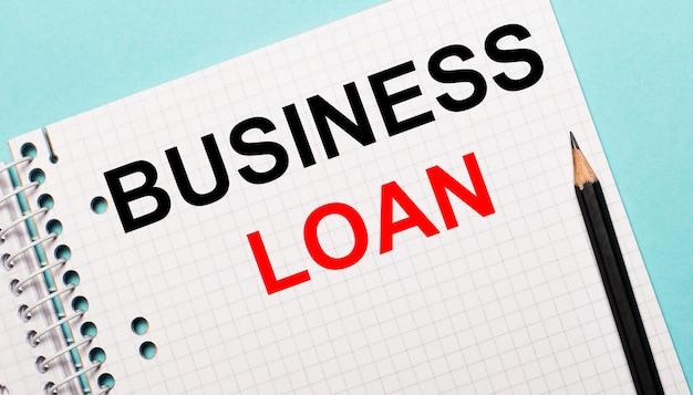Sur fond bleu clair, un carnet à carreaux avec les mots business loan et un crayon noir.