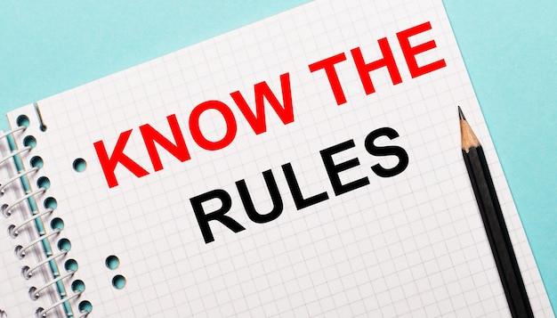 Sur fond bleu clair, un carnet à carreaux avec les mots connaissez les règles et un crayon noir.