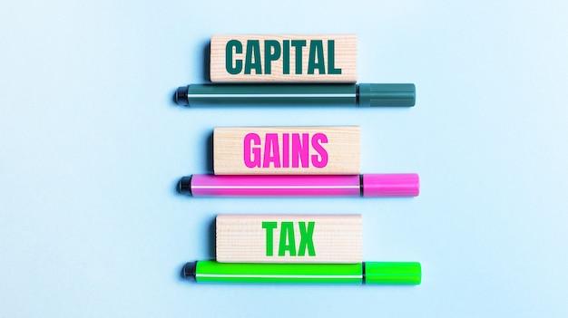 Sur un fond bleu clair, il y a trois feutres multicolores et des blocs de bois avec la taxe sur les gains en capital