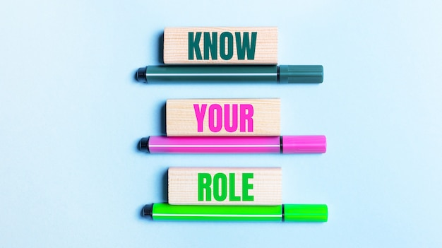 Sur un fond bleu clair, il y a trois feutres multicolores et des blocs de bois avec le texte know your role.