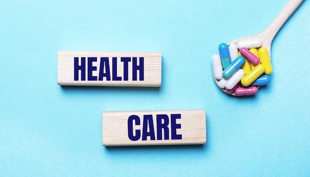 Sur un fond bleu clair, des pilules multicolores lumineuses dans une cuillère et deux blocs de bois avec le texte health care. notion médicale