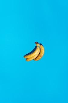 Fond bleu clair sans couture avec motif de bananes jaunes mûres et ombres foncées dures. nouvelle tendance couleur 2021. concept de scène minimal. image de fruits abstraits tropicaux pop art. espace de copie gratuit.