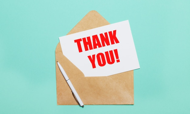 Sur un fond bleu clair se trouve une enveloppe artisanale ouverte, un stylo blanc et une feuille de papier blanche avec le texte merci