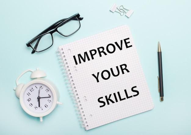 Sur un fond bleu clair se trouvent des lunettes noires et un stylo, un réveil blanc, des trombones blancs et un cahier avec les mots améliorez vos compétences