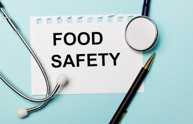 Sur fond bleu clair, un stéthoscope, un stylo et une feuille de papier avec l'inscription food safety.