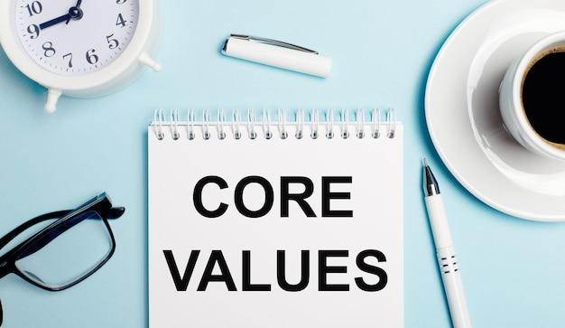 Sur un fond bleu clair, une tasse blanche avec du café, un réveil blanc, un stylo blanc et un cahier avec le texte core values. vue d'en-haut