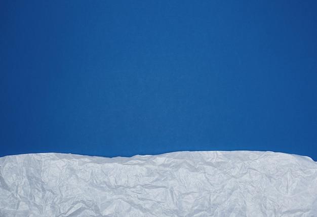 Fond bleu avec des éléments de papier déchiré froissé blanc