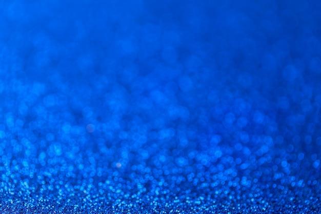 Fond bleu étincelant de petits paillettes, gros plan, toile de fond brillante
