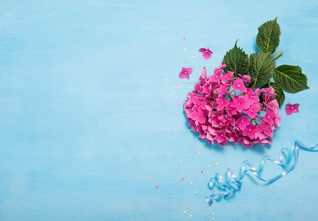 Fond bleu festif avec des fleurs, mise en page avec des fleurs d'hortensia, copie espace