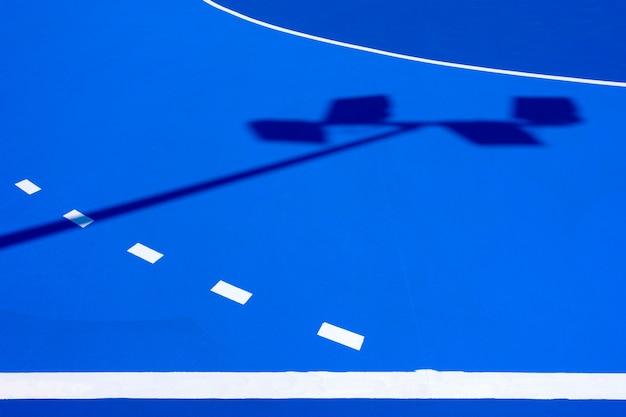 Fond bleu intense, du sol d'un terrain de basket au soleil de midi, avec des lignes droites et des courbes blanches.