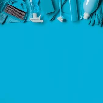Fond bleu avec kit de nettoyage pour le ménage. vue de dessus. espace de copie.
