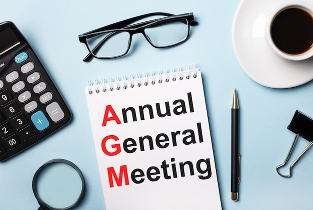 Sur fond bleu, lunettes, calculatrice, café, loupe, stylo et cahier avec le texte assemblée générale annuelle