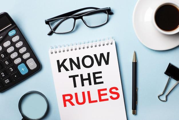 Sur fond bleu, lunettes, calculatrice, café, loupe, stylo et cahier avec le texte connaissez les règles